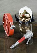 pic of firehose  - A helmet a firehose and a nozzle on the floor in a firestation used by firefighters
