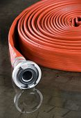 picture of firehose  - A rolled up firehose on the floor in a firestation used by firefighters