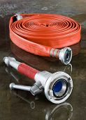 stock photo of firehose  - A rolled up firehose and a nozzle on the wet floor in a firestation used by firefighters - JPG