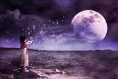 Back View Of Asian Girl Playing With Soap Bubbles On Stone At Seaside. Landscape Of Night Sky With S poster