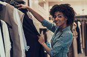 Smiling Young Woman Shopping In Clothing Store. Happy Beautiful Black Girl Choosing Clothes To Buy I poster