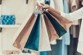 Closeup Young Girl Holding Shopping Bags In Store. Close Up Of Black Girl Holding Shopping Paper Bag poster