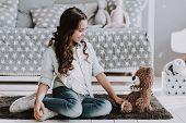 Cute Little Girl Sitting On Carpet With Teddy Bear. Smiling Adorable Little Girl Sitting On Crpet Ne poster