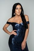 Pretty hispanic teenage girl in a fancy prom or quinceanera dress poster