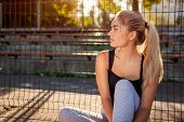 Young Woman Athlete Having Rest After Running On Sportsground In Summer. Girl Chilling Outdoors Sitt poster
