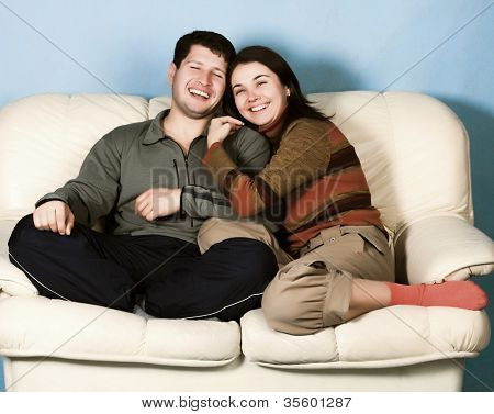 The young couple sitting on a sofa