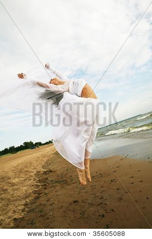 Charmingl girl in white gown jumping on the seashore