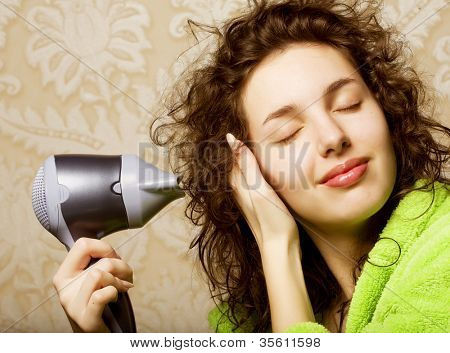 Beautiful woman drying her hair with hairdryer
