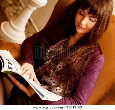 joven mujer leyendo una revista en la hora del té
