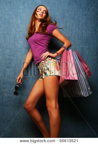 Retrato de una chica feliz de adultos jóvenes con bolsas de colores