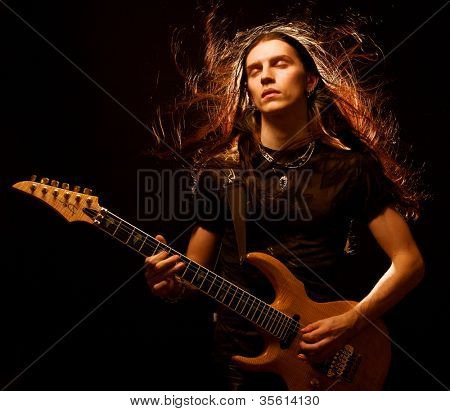 man playing electrical guitar. wind in hair.
