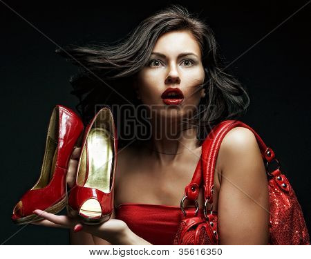 fashion model with red bag and red shoes. on black background.