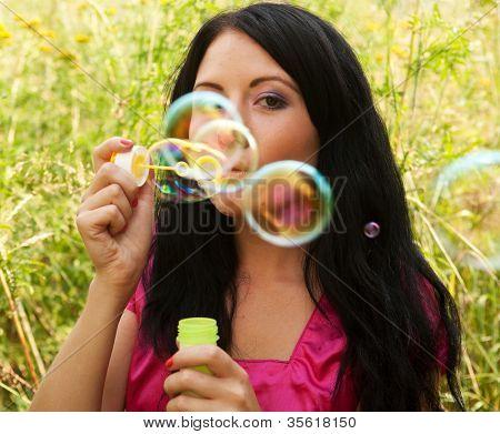 Pretty woman  starts soap bubbles