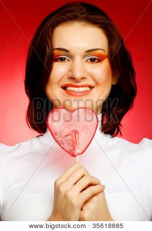 happy woman with heart candy lolly pop. On red background.