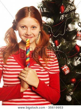 hübsche junge Redhair Frau hält am Stiel Einw. Weihnachtsbaum.