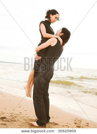 An attractive couple fooling around on the beach