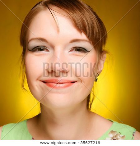 Beautiful young woman face on yellow background