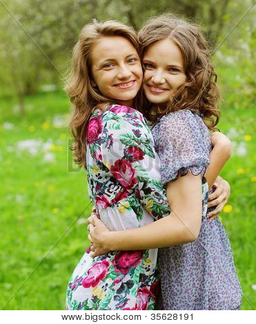 young pretty girlfriends over nature background, in the garden