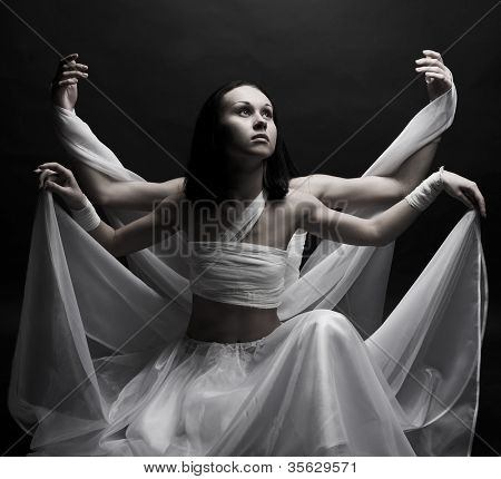 Portrait of two girls in white raiment dancing in semidarkness