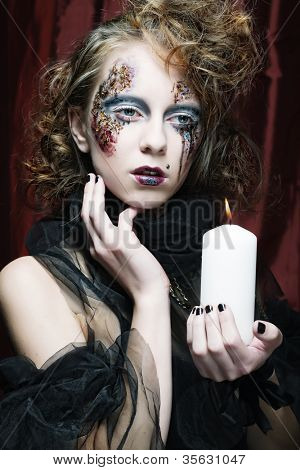Gothic portrait of woman with candle. Halloween theme.