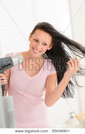 Smiling brunette woman blow-drying long hair in bathroom