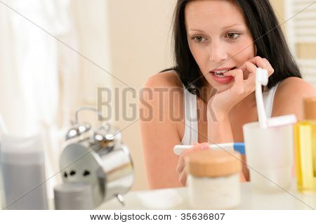Impatient brunette woman in bathroom waiting for pregnancy test result