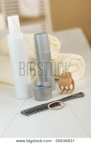 Close-up of hair products and towels in bathroom