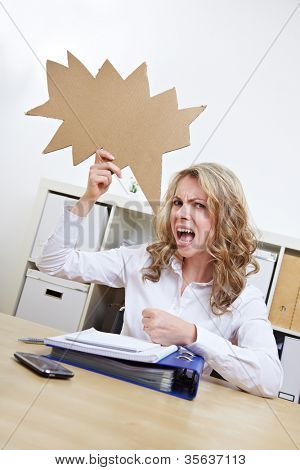 Frustrated woman with empty jagged speech balloon at her desk