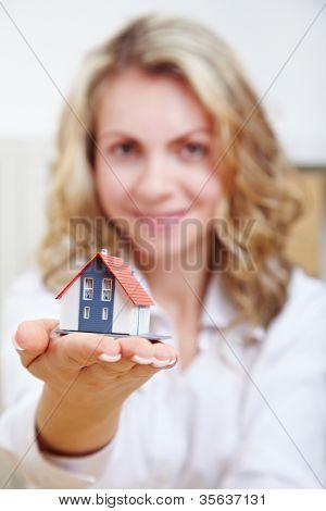 Mulher atraente feliz com casa pequena em sua mão