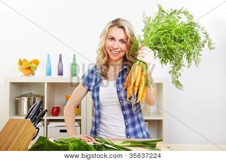 Happy attractive woman with bunch of carrots in the kitchen
