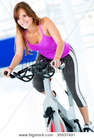 Beautiful woman at the gym doing spinning