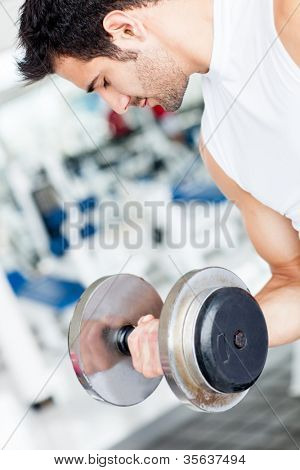 Handsome man working out at the gym lifting weights