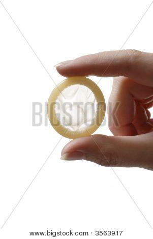 Dedos sosteniendo el condón