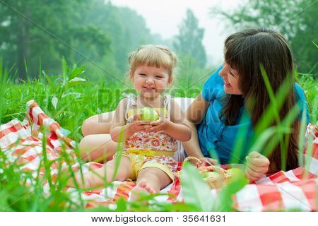 mother and daughter have picnic eating healthy food outdoor