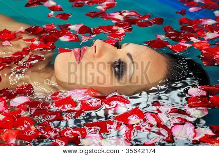 Face of pretty woman floating in swimming pool with petals of rose