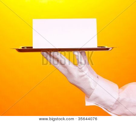 Hand in glove holding silver tray with blank card on yellow background