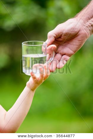 Senior adult giving mug of water to little girl outdoors