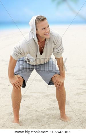 Young happy guy having fun on the beach with nice smile and barefeet in the sand