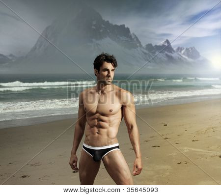 Muscular fit sexy guy on remote scenic beach location with dramatic mountains in background