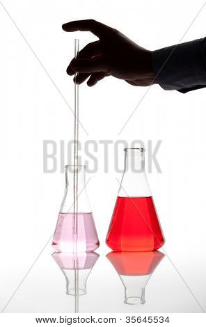 Two Erlenmeyer glass flasks with red colored chemical reagent, isolated