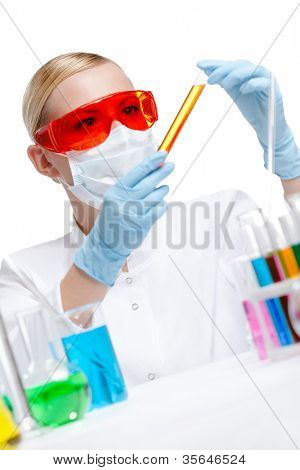 Female chemist in respirator holds a vial with orange liquid, isolated on white