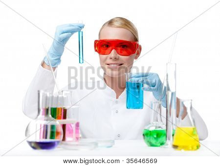 Female doctor in spectacles does some experiments with blue liquid, isolated on white