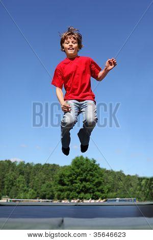 Alegre menino vestido com a t-shirt vermelha pula no trampolim em dia de verão ensolarado