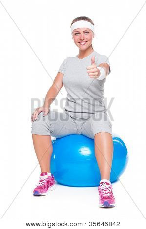 attractive young woman sitting on ball and showing thumbs up