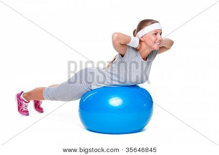 young woman doing exercises on blue ball. studio shot over white background