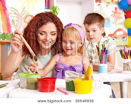 Children with teacher painting at easel in school.