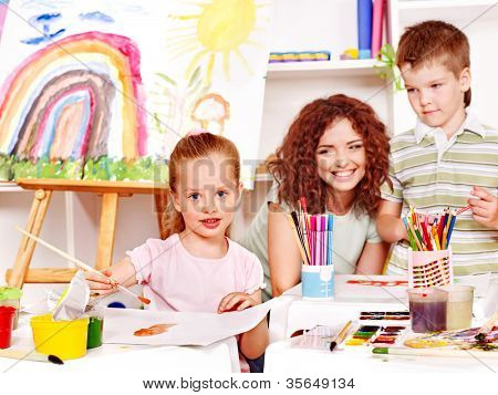 Child with teacher painting at easel in school.