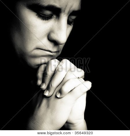 Dramatic black and white portrait of a woman  praying or thinking emerging from a black background
