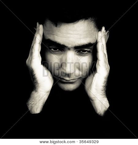 Dramatic black and white portrait of a man suffering a strong headache or depression pressing his forehead with his hands isolated on black