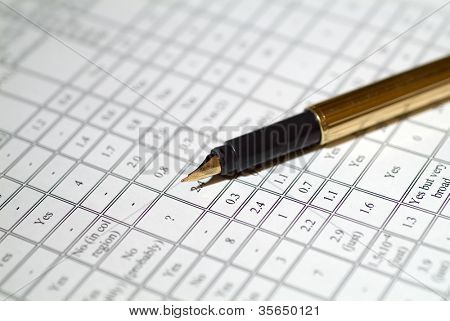 Close up shot of a pen with financial figures.